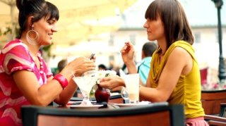 stock-footage-two-female-friends-with-mobile-phone-in-bar-outdoors-camera-stabilizer-shot
